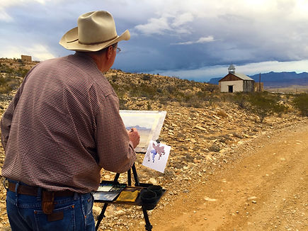 artist tim oliver at easel painting adobe church in terlingua on stormy day