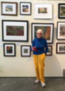 artist anne eckley with wall of thread paintings at old spanish trail gallery