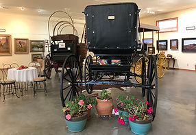 inside old spanish trail gallery and museum, buggy, chuckwagon geraniums table and wall art