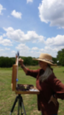artist dina gregory under cumulus clouds in green field with easel and paints