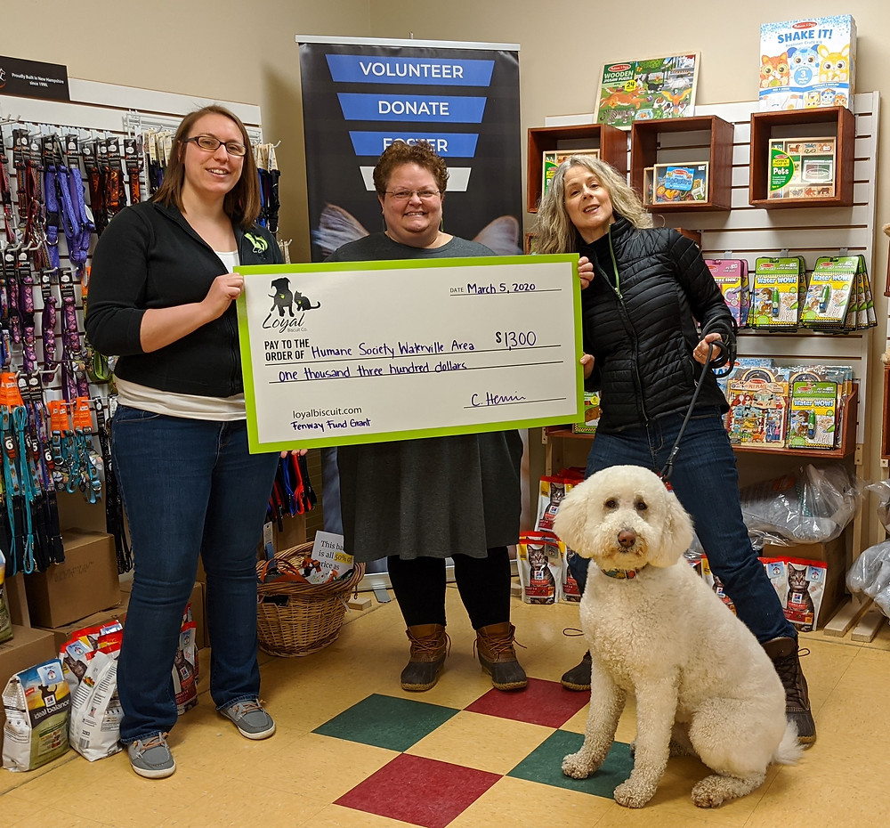 Chelsie Herrin of the Waterville Loyal Biscuit Co. presents a check to Lisa Oakes, HSWA director and Dianna Demers, HSWA board member with her dog Sadie.