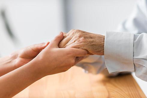 nurse-holding-senior-man-s-hands-for-comfort.jpg