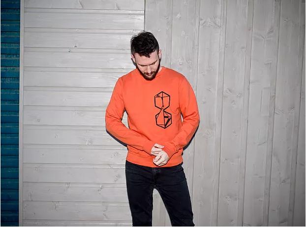 man wearing an orange sweater