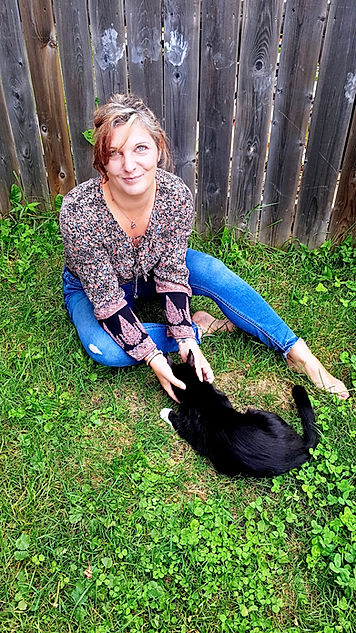 Woman sitting in grass with black cat