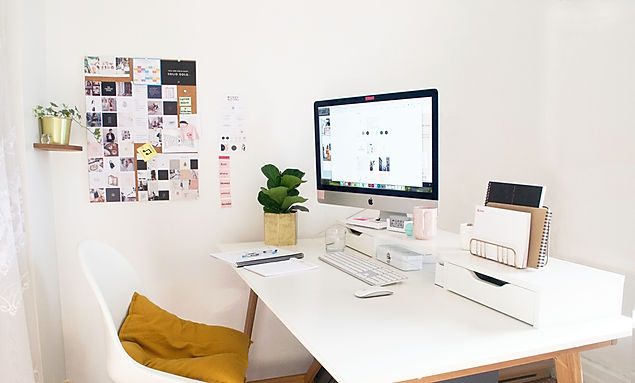 Office space with computer on desk, photos and designs on the walls