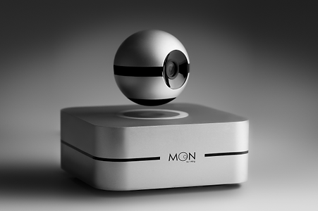 moon ist auf den ersten blick eine überwachungskamera für zuhause. dabei schwebt sie durch magneten auf ihrer basisstation und lässt sich dadurch mittels der app leicht in die gewollte richtung steuern. die eingebauten mikrofone nehmen die richtung wahr, aus der ein geräusch kommt und bewegt die kameralinse dahin. dazu hat das gerät temperatur-, co2, feuchtigkeits- und lichtsensoren, mit denen du den zustand deiner wohnung im blick hast. zur installation sind keine kabel notwendig.