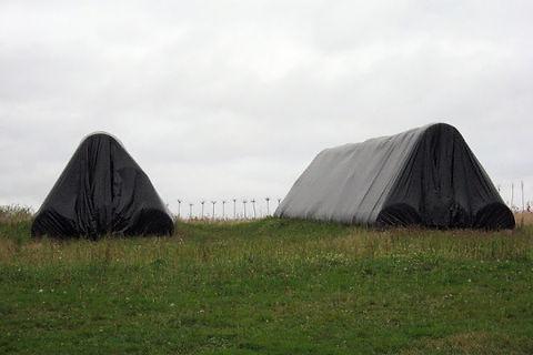 Deux stoks de balles de foins recouvert d'une bâche noire au milieu d'un pré