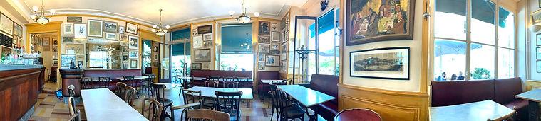 Photo panoramique à l'intérieur vide du Café Bellecour avec beaucoup de toiles et de dessins sur les murs. Les ouvertures donnent sur les terrasses.