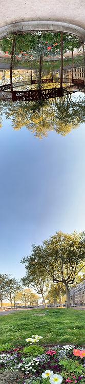 Photo panoramique verticale montrant le terre plein de l'axe Nord/Sur quai Jean Moulin, au niveau de la rue Menestrier. Il y a aussi un kiosque en haut de l'image
