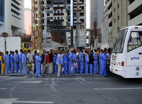 Des ouvriers étrangés habillés en bleu en file indienne attendent de monter dans un bus blanc à Dubaï