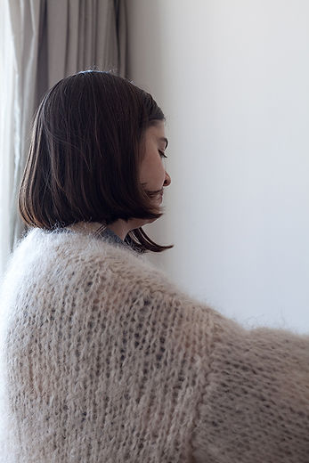 Portrait de Lise Bisleau de 3 quart de dos avec un énorme chandail