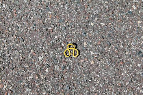 Photo d'un elastique formant 3 boucles sur lui même sur un trottoir