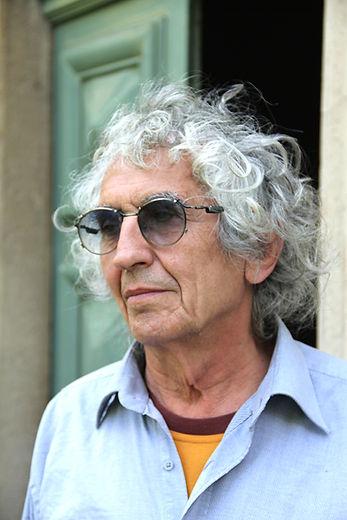 Portrait en plan rapproché de Pierre Casalegno devant une porte à moitié ouverte