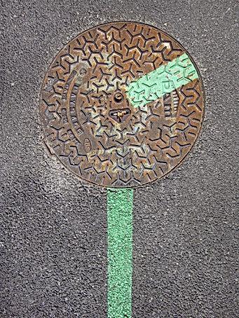 Trace de peinture sous une plaque de trottoir avec sur cette plaque la continuation de cette trace de peinture qui montre la plaque a tournée.