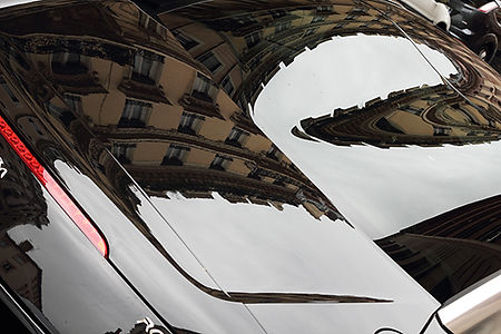 Reflexion d'immeubles sur la vitre arrière d'une voiture. La déformation dûe à la réflexion déforme les immeubles et les courbe