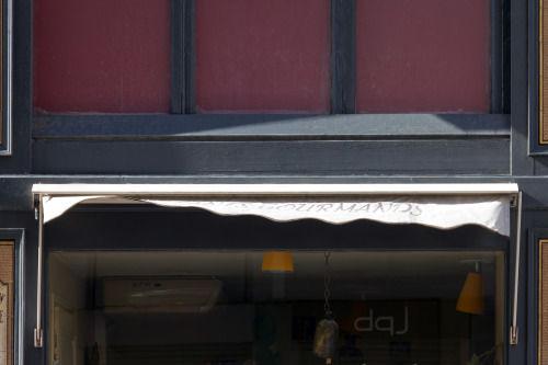 Store relevé d'un magasin, avec le nom gourmands ballotté par le vent.