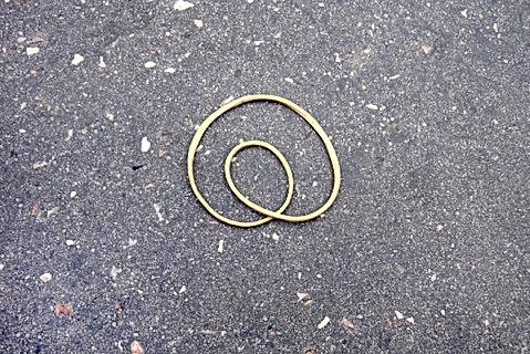 Photo d'un elastique formant une arobase sur un trottoir