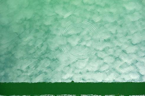 Vue en plongée, une surface d'eau verte, avec des ondes rondes réfléchit le ciel et les nuages.
