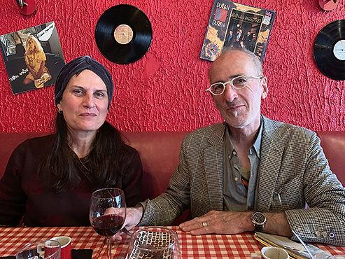 Portrait de Sonja Dicquemare et Nicolas Wiplier atablés dans un restaurant avec des disques sur le mur rouge.