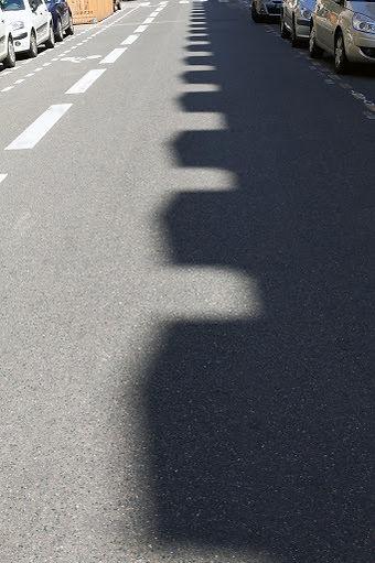 une ombre de créneaux se dessine sur une rue, parallèlement à une piste cyclable
