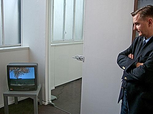 Portrait de Philippe Ramette regardant une vidéo