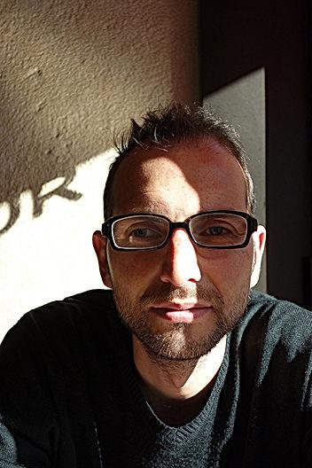 Portrait de Almiro Soares avec des lunettes, un pull noir, une barbe naissante.