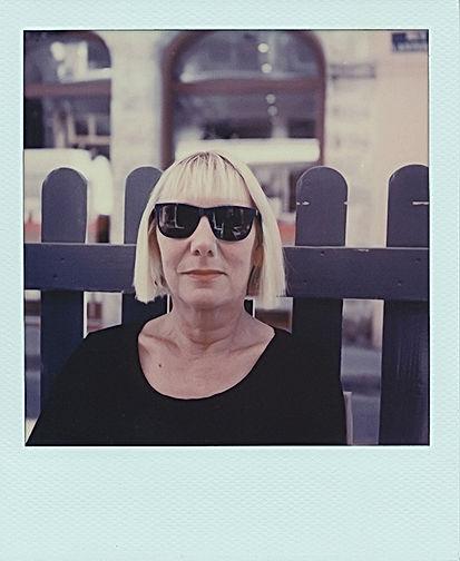 Portrait polaroïd en plan rapporché d'Isabelle Antoine en pull noir et devant une barrière en bois en ville