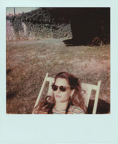 Portrait polaroïd en plan rapproché de Charlotte Denamur sur une chaise longue avec des lunettes de soleil, sur une pelouse