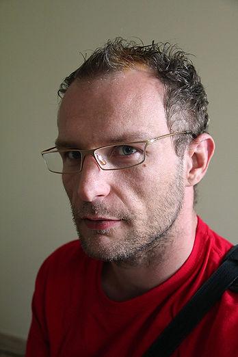 Portrait en gros plan de Anthony Coursier avec des lunettes et la barbe naissante
