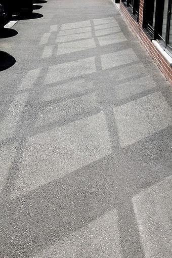 Réverbération du soleil tapant sur des vitrines de magasins sur un trottoir