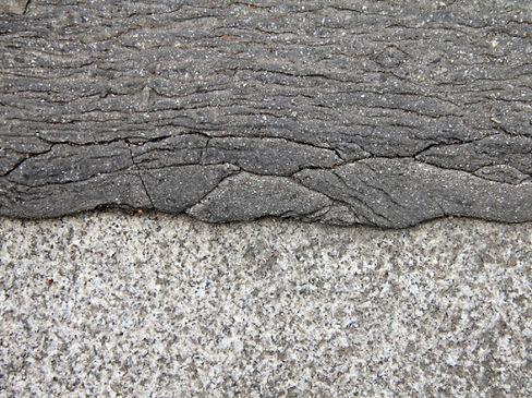 Goudron d'un trottoir en pente qui avec la chaleur déborde sur la bordure en pierre du trottoir