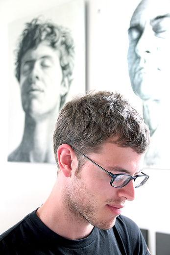 Portrait de Joël Riff avec derrière lui de grands dessins de Pierre David