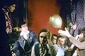 Image du film Viva de Georges Rey. Regroupement de personnes dans une atmosphère décadente avec un ballon jaune qui vole avec un mur rouge dans à l'arrière plan