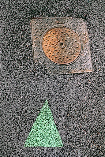 photo d'une trace de peinture triangulaire désignant une plaque circulaire inscrite dans un support carré sur un trottoir