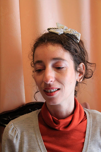 plan rapproché de Julie Rodriguez-Malti devant un rideau pêche avec un col roulé orange sanguine.
