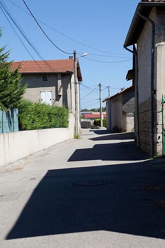 Les bâtiments des fermes projettent leur ombre sur une rue rurale à Sablons