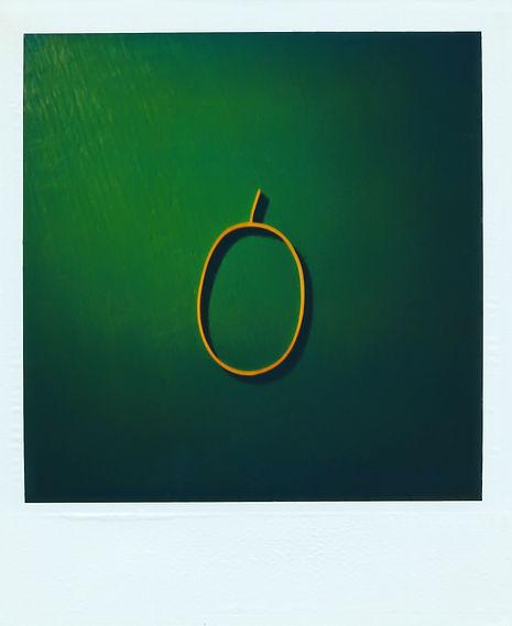 Photo polaroid d'un petit elastique oval sur fond vert avec une excroissance sur le haut de l'elastique