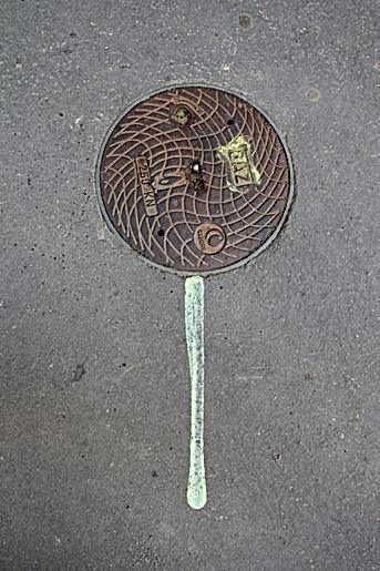 Photo d'une trace de peinture dessous une petite plaque de gaz sur le trottoir