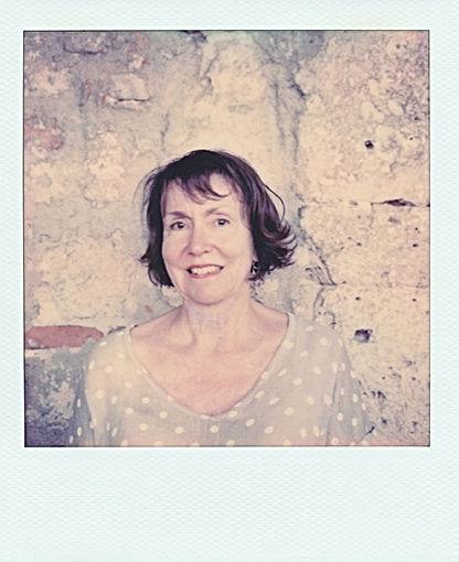 Portrait polaroid en plan rapprochéde Elizabeth Blachère devant un mur brut en pierre. Elle porte un t-shirt à poids