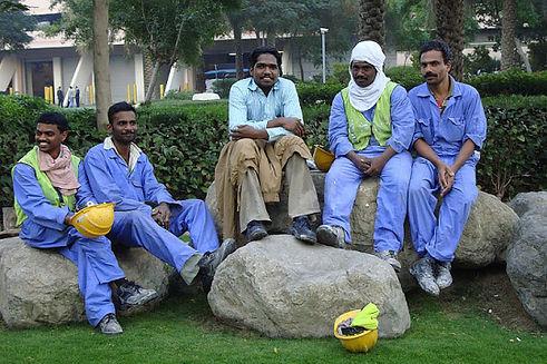 Des ouvriers souriants étrangés à Dubaï se reposent sur des rochers