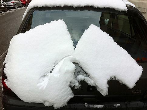 A l'arrière d'une voiture, en glissant, un bloc de neige s'est fendu en deux.