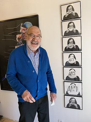 Portrait de Jean-Claude Guillaumon souriant, devant une de ses oeuvres, avec un gilet bleu.