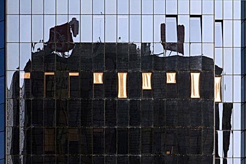 Façade d'un immeuble en verre avec une rangée de stores plus ou moins baissé aux couleurs or.