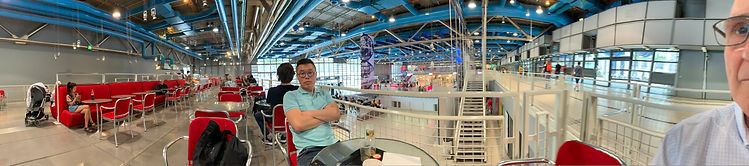 Photo panoramique du café Mezzanine, au premier niveau du centre Pompidou, avec vue sur l'entrée et la tuyauterie au plafond avec Tao Zuo au centre de la photo