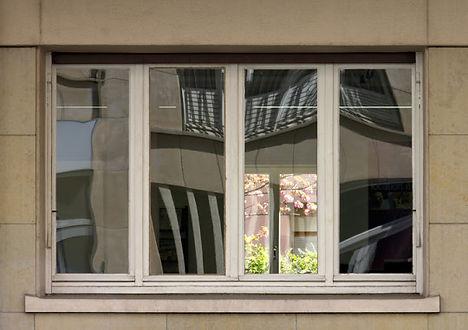 Fenêtre extérieure vue de face dans laquelle se reflete l'immeuble d'en face. On voit aussi au fond de la pièce un jardin avec des arbres en fleurs