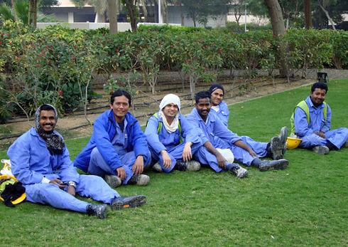 Des ouvriers souriants étrangés à Dubaï se reposent sur des pelouses.