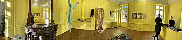 Photo panoramique d'une expostion à l'Attrape Couleurs avec les murs en jaune et deux personnes qui nous regardent, exposition The Yellow WallpaperdeFlorent Dubois,Eva GaltieretBénédicte Thoraval