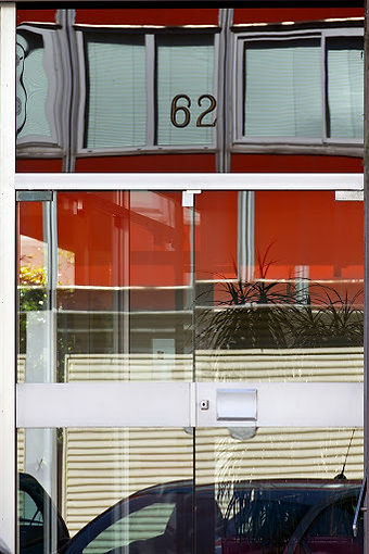 Porte vitrée au numéro 62 qui reflète l'extérieur tout en laissant apercevoir l'intérieur
