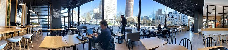 Photo panoramique à l'intérieur de la chaine de café/restaurant Fruisy à Garibaldi. Des personnes assises travaillent sur des ordinateurs