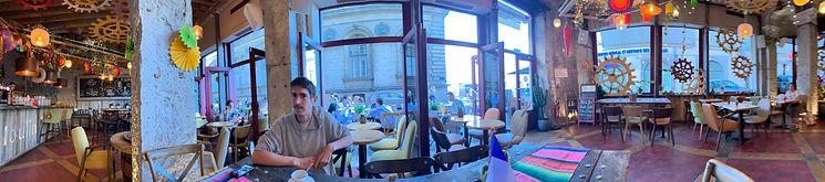 Photo panoramique à l'intérieur du bar Le Moulin 1883 avec à l'extérieur une partie de la mairie et la place des Terraux